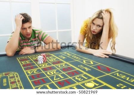 Young man and woman losing on roulette table - stock photo