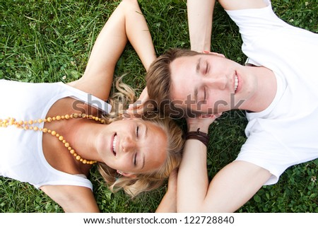 Young man and woman lying on grass head to head - stock photo