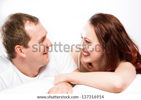 Young man and woman lying together in bed, smiling and happy