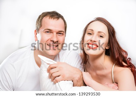Young man and woman lying together in bed, smiling and happy - stock photo