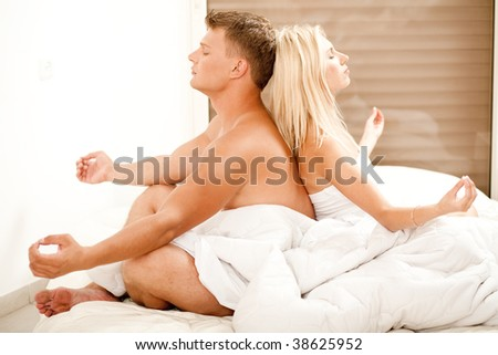 Young man and woman meditating in bed - stock photo