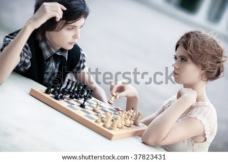 Young man and woman playing chess. Soft white colors and shallow dof. - stock photo