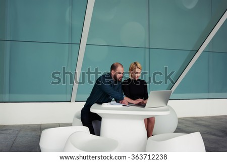Young man and woman reading comments from clients about their new project through net-work on laptop computer, team of creative designers working together on net-book while sitting in office interior  - stock photo