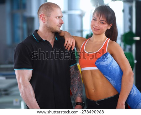 Young man and woman relaxing in sports outfits at the gym - stock photo
