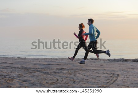 Young man and woman running along the waterfront - stock photo