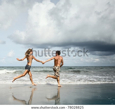 Young man and woman running together on wet sand by sea edge on dark sky background - stock photo
