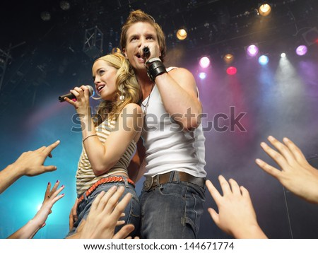 Young man and woman singing on stage in concert in front of adoring fans - stock photo