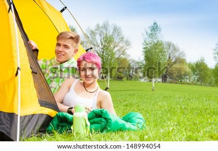 Young man and woman sitting in the tent in the park on sleeping bag - stock photo