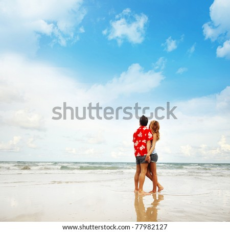 Young man and woman standing on wet sand at sunny day and looking to sea