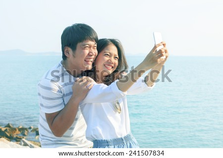 young man and woman take a photo by smart phone at sea side use for new people life style and technology activities  - stock photo
