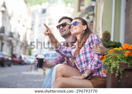 Young man and woman together sitting on stairs of fashionable shop. Gilr showing to her boy-friend something in the sky.