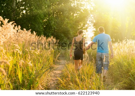 Young man and woman walking holding hands in the forest