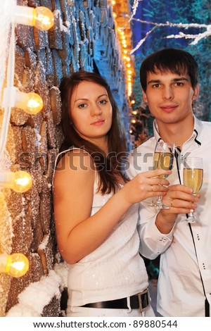 Young man and woman wearing white shirts with glasses of champagne stand near stack of wood and look at camera - stock photo