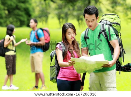 young man and woman, with backpacks, reading a map. - stock photo