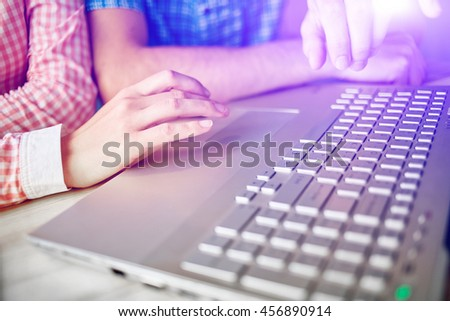 young man and woman with laptop typing on the keyboard in cafe. palm, tablet PC and laptop closeup. small depth of field