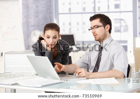 Young man and woman working together in office, looking at laptop, sitting at desk.