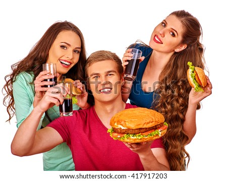 Young man and women holding big hamburger and glass of cola . Fastfood concept. Isolated. Women feeding man fast food.