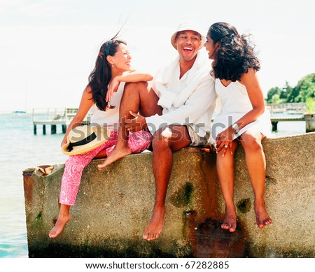 Young man and women relaxing near shore - stock photo