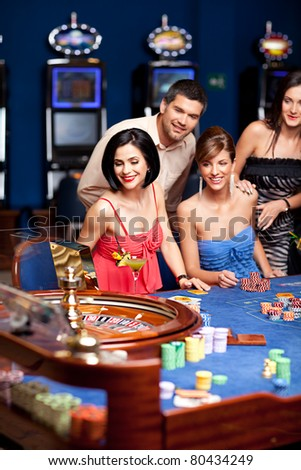 young man and women smiling and playing roulette