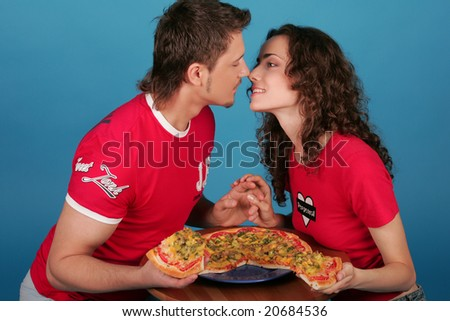 Young man and young woman kissing with pizza in their hands