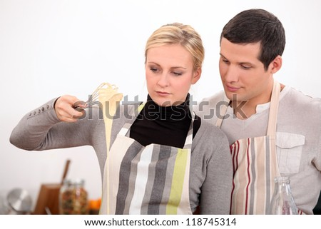 Young man and young woman making a cake dough - stock photo