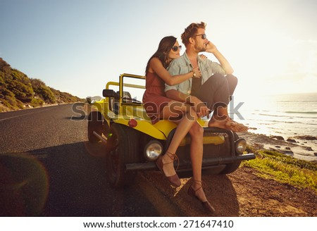 Young man and young woman on road trip on a beautiful summer's day.