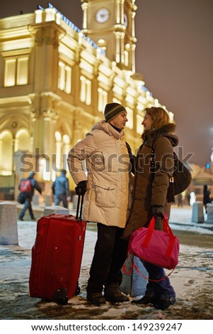 Young man and young woman stand on railway platform in winter evening, looking at each other