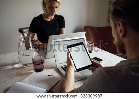 young man and young woman working opposite each other with laptops. male person using digital tablet with blank copy space screen for your information