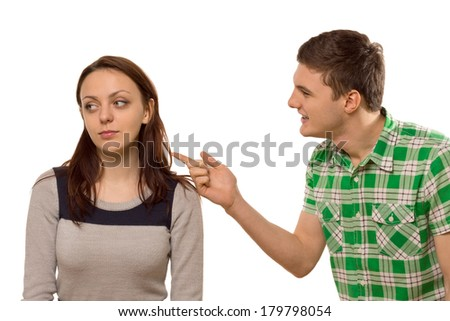 Young man arguing with his girlfriend pointing his finger at her as she turns aside in indifference, isolated on white