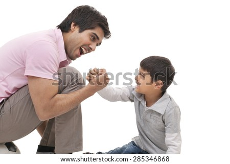 Young man arm wrestling with his son over white background - stock photo
