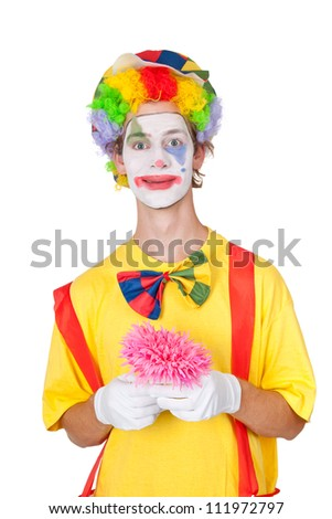 Young man as clown holding pink plastic flower - isolated