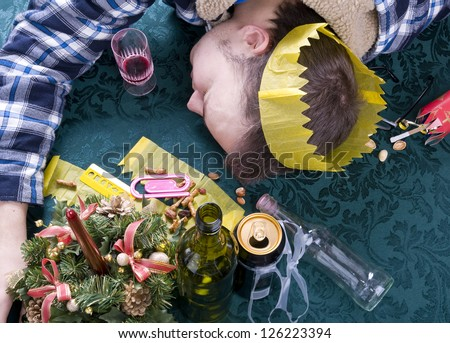young man asleep with head on table after party - stock photo