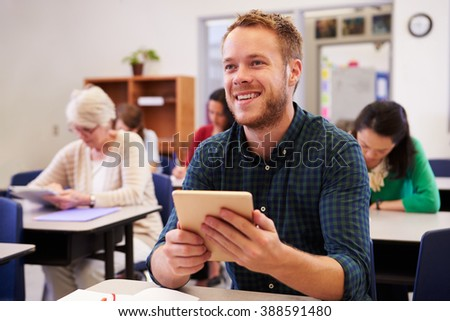 Young man at an adult education class looking up at board