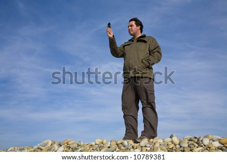 Young man at beach taking photo on the phone