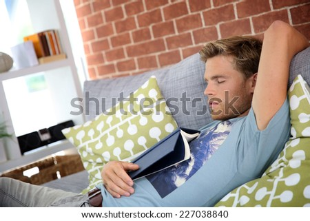 Young man at home taking a nap in sofa - stock photo