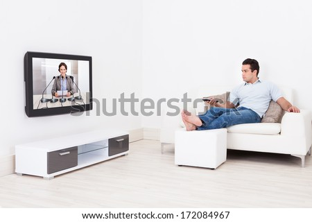 Young Man At Home Watching News On Television