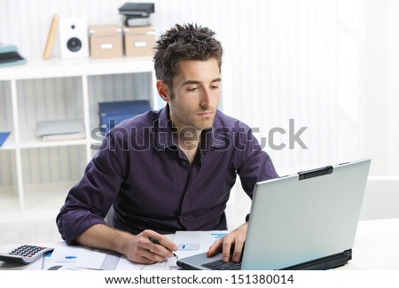Young man at home working on laptop - stock photo