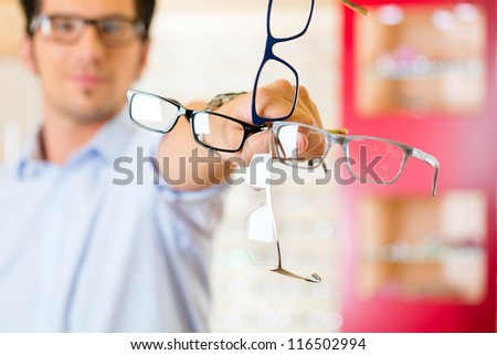 Young man at optician with glasses, he might be customer or salesperson - stock photo