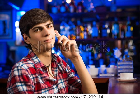young man at the bar on the phone and drinking coffee