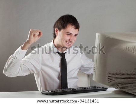 young man at the computer enjoys raising his hands - stock photo