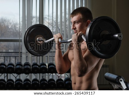 Young man at the gym lifting performs an exercise for biceps with a curved barbell