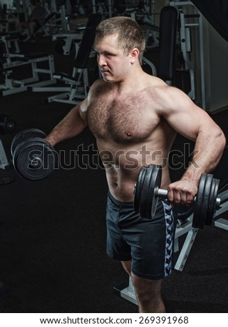 Young man at the gym to exercise the deltoid muscle of the shoulder, lifting dumbbells to the sides. Toning, hard light. - stock photo