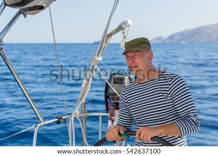 Young man at the helm on the sailing boat. Ship controls during sea yacht race.
