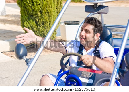 young man at  wheel of buggy shows  hand aside - stock photo
