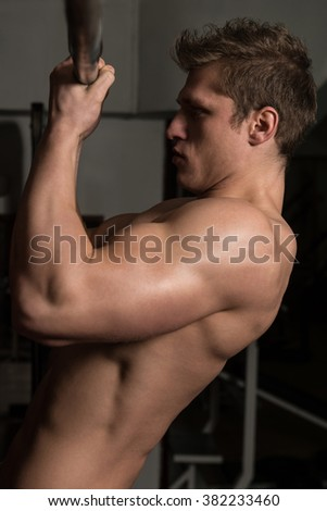 Young Man Athlete Doing Pull Ups For Biceps - Chin-Ups In The Gym