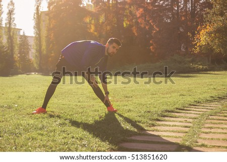 young man athlete football soccer player stretching leg. outdoors park, sunny autumn day.