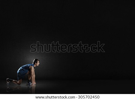 Young man athlete standing in start pose - stock photo