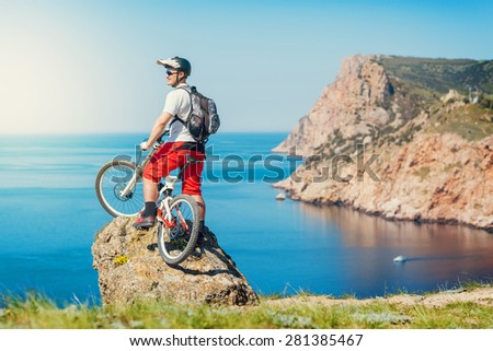 Young man athlete standing on top of a mountain with bicycle and enjoying view.