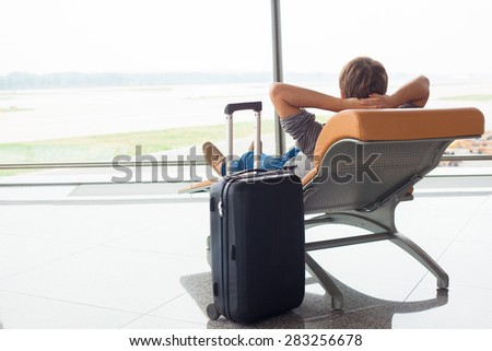young man awaiting his flight with confort at airport terminal. transportation concept - stock photo