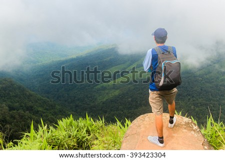 young man backpacker enjoy the view at mountain peak on cloudy day.